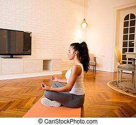 mujer se sentar, en, piso, en casa, hacer, yoga, meditación