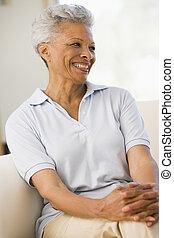 mujer se sentar, en, sala, sonriente