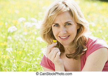 mujer se sentar, flor, tenencia, aire libre, sonriente