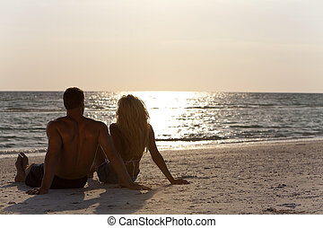 mujer se sentar, pareja, joven, playa puesta sol, hombre