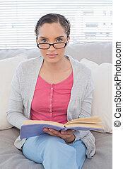 mujer se sentar, sofá, relajado, libro, tenencia
