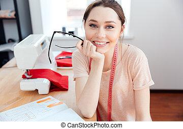 mujer se sentar, trabajo, alegre, sonriente, costurera