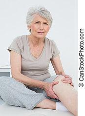 mujer, Sentado, examen, rodilla, tabla, 3º edad, doloroso