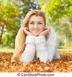 mujer sonriente, acostado, en, un, otoño sale