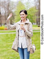 mujer sonriente, café de bebida, en el estacionamiento