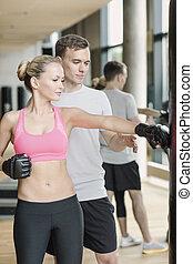 mujer sonriente, con, entrenador personal, boxeo, en, gimnasio