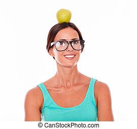 mujer sonriente, con, un, manzana, en, ella, cabeza