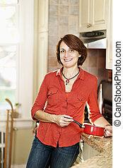 mujer sonriente, en, cocina, en casa