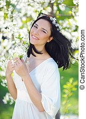 mujer sonriente, en, primavera, jardín