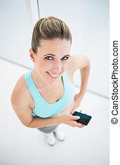 mujer sonriente, en, ropa de deporte, utilizar, teléfono móvil
