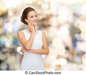 mujer sonriente, en, vestido blanco, llevando, timbre de...