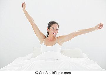 mujer sonriente, estirar los brazos, en cama