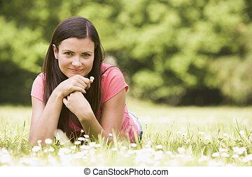 mujer sonriente, flor, acostado, aire libre