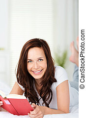 mujer sonriente, lectura, en cama