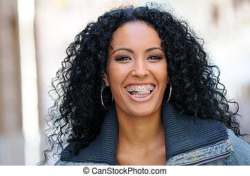 mujer sonriente, negro, joven, fierros