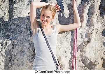 mujer sonriente, posición, delante de, roca