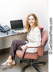 mujer sonriente, sentado, en, escritorio de oficina