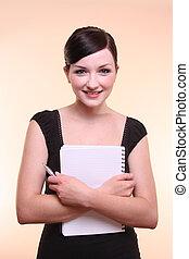 mujer sonriente, tenencia, cuaderno, y, pluma
