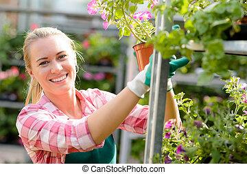 mujer sonriente, trabajando, en, centro de jardín, soleado