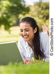 mujer sonriente, usar la computadora portátil, en el estacionamiento
