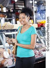 mujer sonriente, utilizar, teléfono celular, en, tienda de comestibles, tienda