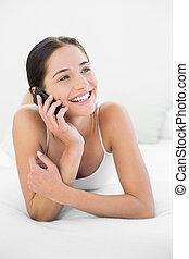 mujer sonriente, utilizar, teléfono móvil, en cama