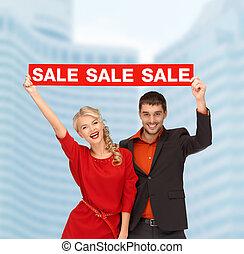mujer sonriente, y, hombre, con, rojo, muestra de la venta