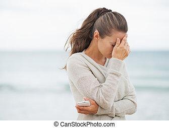 mujer, suéter, joven, teléfono celular, enfatizado, playa