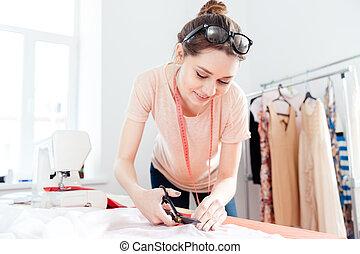 mujer, tela, corte, tijeras, sonriente, costurera, blanco