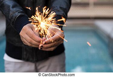mujer, tenencia de la mano, sparkler