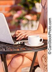mujer, trabajando, sentado, imagen, wi-fi., cortado, mientras, al aire libre, advantages, libre, utilizar, café, computador portatil