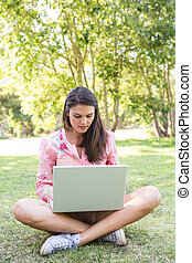 mujer usando la computadora portátil, en el estacionamiento