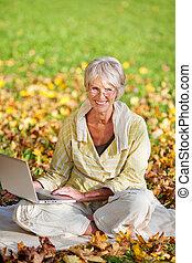 mujer usando la computadora portátil, mientras, sentado, en el estacionamiento