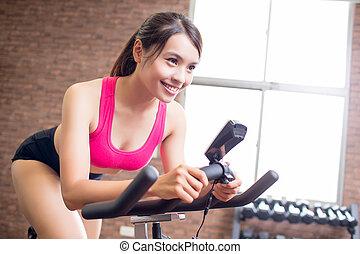 mujer, uso, bicicleta ejercicio