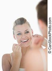 mujer, utilizar, seda dental, delante de, espejo