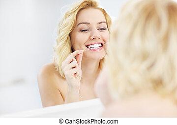 mujer, utilizar, seda dental