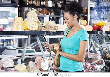 mujer, utilizar, teléfono celular, en, tienda de comestibles, tienda