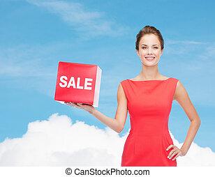 mujer, venta, joven, señal, sonriente, vestido, rojo
