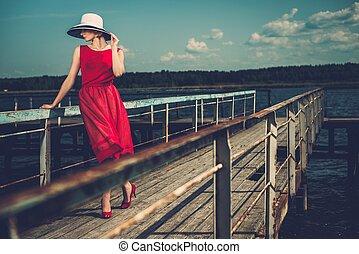 mujer, viejo, de madera, elegante, sombrero, posición, muelle, vestido rojo, blanco