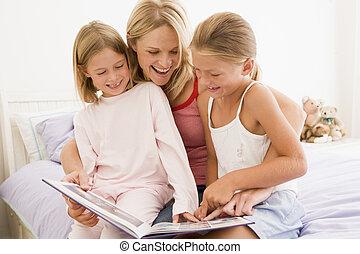 mujer, y, dos, niñas jóvenes, en, dormitorio, libro de lectura, y, sonriente