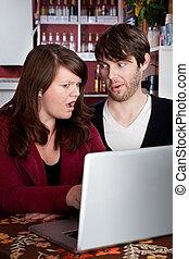 mujer y hombre, mirar fijamente, en, incredulidad, en, un, computadora, computador portatil
