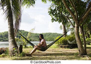mujeres asiáticas, sentarse, y, relajante, en, muebles, hamaca, ahorcadura, entre, árboles de palma, en, jardín, de, recurso, frente, de, el, playa