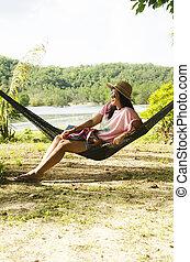 mujeres asiáticas, sentarse, y, relajante, en, muebles, hamaca, ahorcadura, entre, árboles de palma, en, jardín