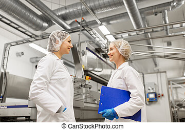 mujeres felices, technologists, en, helado, fábrica