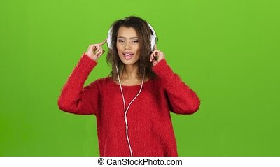 Mulatto girl dances and sings with headphones on green screen
