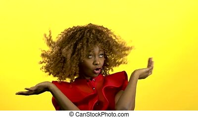 Mulatto girl jumping and having fun with music. Yellow background. Slow motion