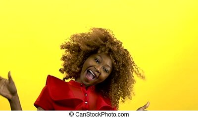 Mulatto girl makes flies hair. Yellow background. Slow...
