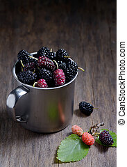 Mulberries on wooden background