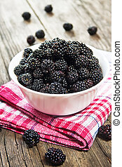Mulberry berries in a bowl on wooden nable