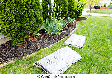 Mulching flowerbeds around the house with bags of organic...